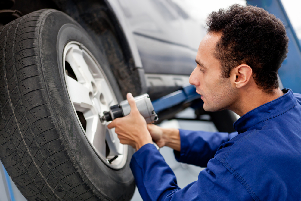 Male mechanic at a car garage fixing a wheel