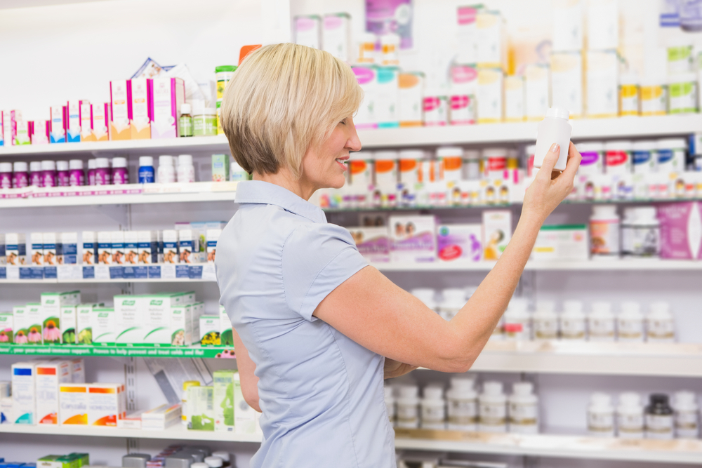 Pretty blonde customer looking at medicine in the pharmacy-1